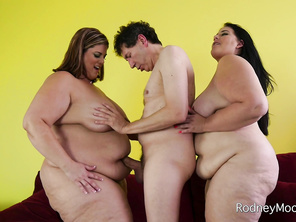 Rodney fondles the big boobs of one babe while the other strokes his cock.