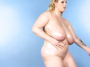 Renee stands against a bare blue background, the better to examine and focus on her amazing jugs and sexy face.