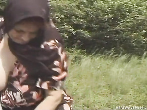 A young stud is walking through the forest when he spies an old lady with a scarf around her head working on the fields.