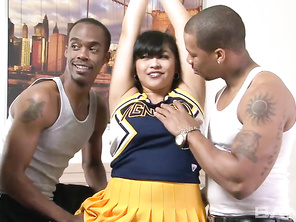 The gorgeous, Asian cheerleader Mika Tan, will be getting her partially shaved snatch licked by one of her interracial sex partners, while the other is sucking on the nipples of her huge, home grown melons.