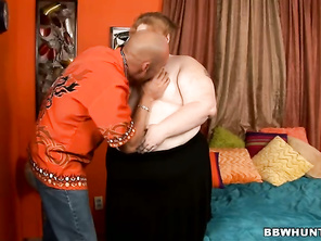 Ruby Passion takes charge in this scene by taking off her clothes and munching on her partner's black cock.