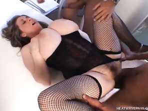She wears some skimpy black lingerie, and she squats down to take turns sucking each guy's hard cock.